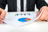 Businessman analysing a set of bar and pie graphs — Stock Photo