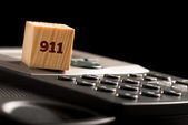 Wooden cube with 911 on a phone keyboard — Stock Photo