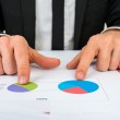 Hands of a businessman analysing two pie graphs — Stock Photo #60750149