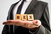 Businessman holding wooden alphabet blocks reading Sex — Stock Photo