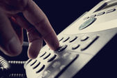 Person dialing out on a telephone — Stock Photo