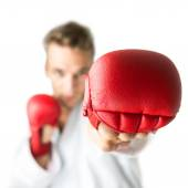 Kickboxer with red boxing gloves performing a martial arts punch — Stock Photo