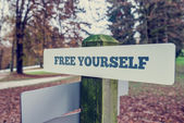 Rustic signboard outdoors in an autumn park with words Free your — Stock Photo