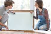 Young couple putting together self assembly furniture — Stok fotoğraf