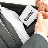 Businessman removing or placing a card with word Vision — Stock Photo