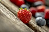 Ripe red strawberry on a rustic wooden table — Stock Photo