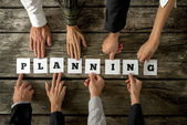 Eight business people assembling the word Planning — Stock Photo