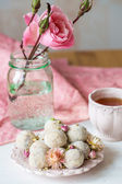 Homemade coconut balls decorated with little pink flowers — Stock Photo