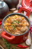 Vegetable stew with sausages in a red pan, vertical — Stock Photo