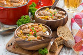 Vegetable stew with sausages in a wooden bowl on board and bread — Stockfoto