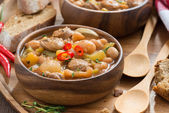Vegetable stew with sausages in a wooden bowl — Stockfoto