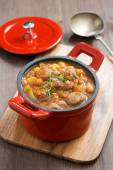 Delicious vegetable stew with sausages in a red pan — Stock Photo