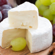 Fresh camembert on a wooden board and grapes, close-up — Stock Photo #52577475