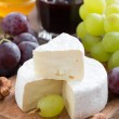 Fresh camembert on a wooden board and grapes, vertical — Stock Photo #52578869