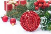 Christmas composition with red ball, fir branches and gifts — Stock Photo