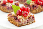 Berry tart with fresh redcurrants and mint on white plate — ストック写真
