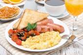 Scramble eggs with tomatoes, sausage and toast on a plate — Stock Photo