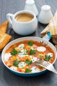 Fried quail eggs in tomato sauce with toasts in a frying pan — Stock Photo