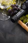 Bottle of red wine, empty glass and grapes on wooden background — Stock Photo