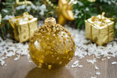 Christmas ball and spruce branches on a wooden background — Stock Photo