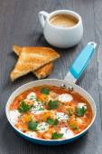 Fried quail eggs in tomato sauce with toasts and coffee — Stock Photo