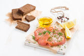 Salted salmon, bread and ingredients on a wooden board — Stock Photo