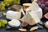 Delicacy soft cheeses, fruit and crackers, close-up — Stock Photo