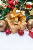 Golden gift box and Christmas tree decorations, vertical — Stock Photo