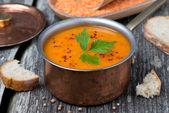 Soupe épicée aux lentilles rouges dans une casserole de cuivre sur une table en bois — Stockfoto