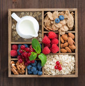 Wooden box with breakfast items - oatmeal, granola, nuts, berry — Stock Photo