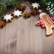 Wooden background with fir branches, cookies and gingerbread man — Stock Photo #56646639