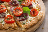 Delicious pizza with salami and tomatoes on a wooden board — ストック写真