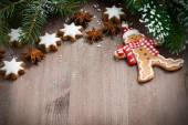 Wooden background with fir branches, cookies and gingerbread man — Stock Photo