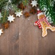 Wooden background with fir branches, cookies and gingerbread man — Stock Photo #56838989