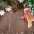 Wooden background with fir branches, cookies and gingerbread man — Stock Photo #57434161