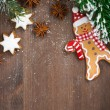 Wooden background with fir branches, cookies and gingerbread man — Stock Photo #57434187