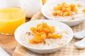 Plates of oatmeal with fresh apricots and nuts, orange juice — Stock Photo