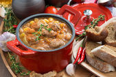 Vegetable stew with sausages in a red pan — Photo