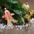 Gingerbread man in the snow, fir branches and decorations — Stock Photo #57716021