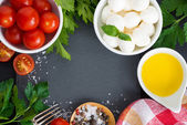 Mozzarella, ingredients for the salad and black background — Stock Photo