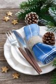 Christmas table setting with spruce branches and stars on wood — Stock Photo