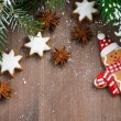 Wooden background with fir branches, cookies and gingerbread man — Stock Photo #59074979