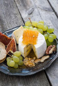 Fresh camembert with honey, grapes and crackers on a plate — Stock Photo