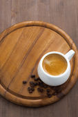 Cup of espresso on a wooden tray, vertical, top view — Стоковое фото
