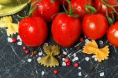 Dark background with cherry tomatoes and ingredients — Stock Photo
