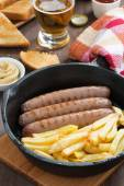 Grilled sausages with French fries, toast and beer, close-up — Stock Photo