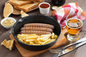 Grilled sausages with French fries  in a frying pan, toasts — Stock Photo