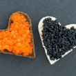 Toast with red and black caviar in the form of heart on dark — Stock Photo #60509535