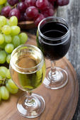 Glass of white and red wine, fresh grapes on a wooden board — Stock Photo