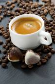 Cup of espresso, coffee beans background and chocolate candies — Stock Photo